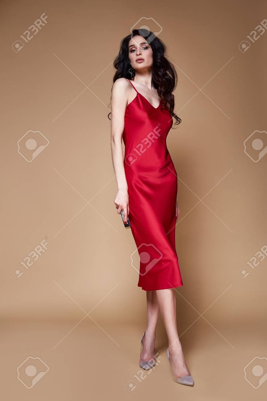 9ca531dbb2e2 Beautiful sexy young elegant woman brunette hair with evening makeup wearing  long red silk dress high