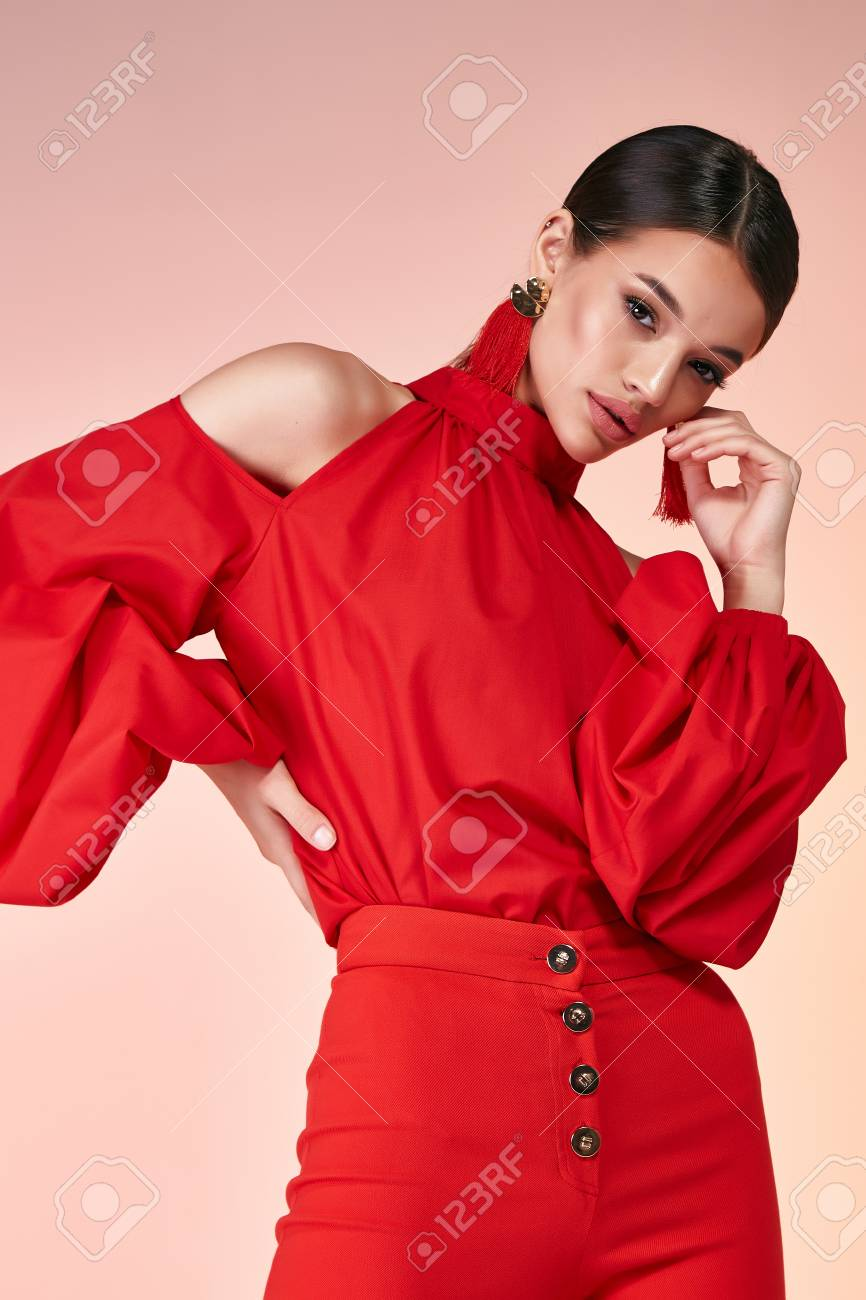 Pretty beautiful elegance woman fashion model glamor pose wear red color trousers silk blouse clothes for party summer collection makeup hair style brunette success accessory bag jewelry studio. - 106827302