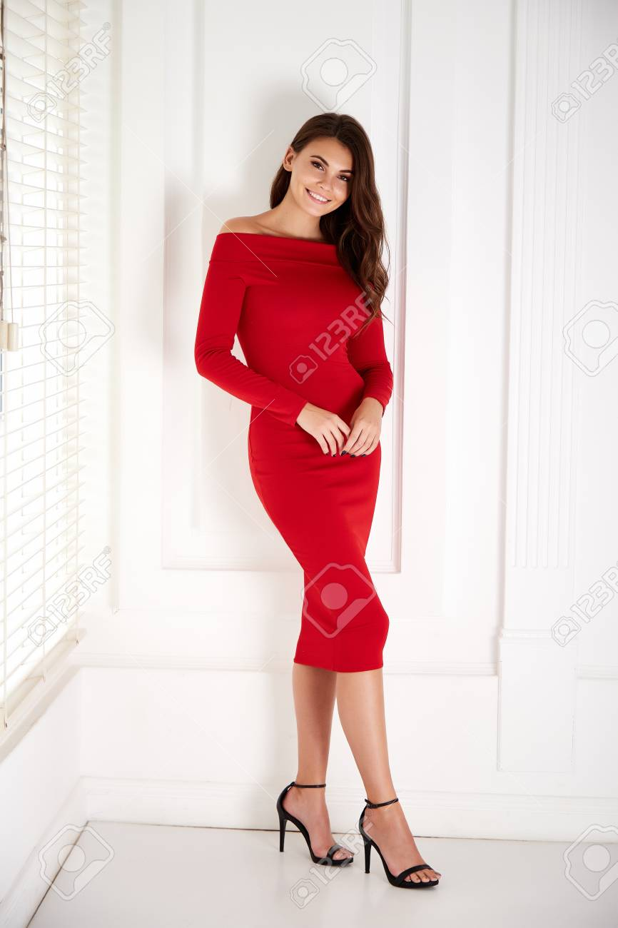 Beautiful young business woman brunette hair with evening make-up wearing a red skinny dress and high-heeled shoes business clothes for meetings and walks fall collection perfect body shape. - 109549584