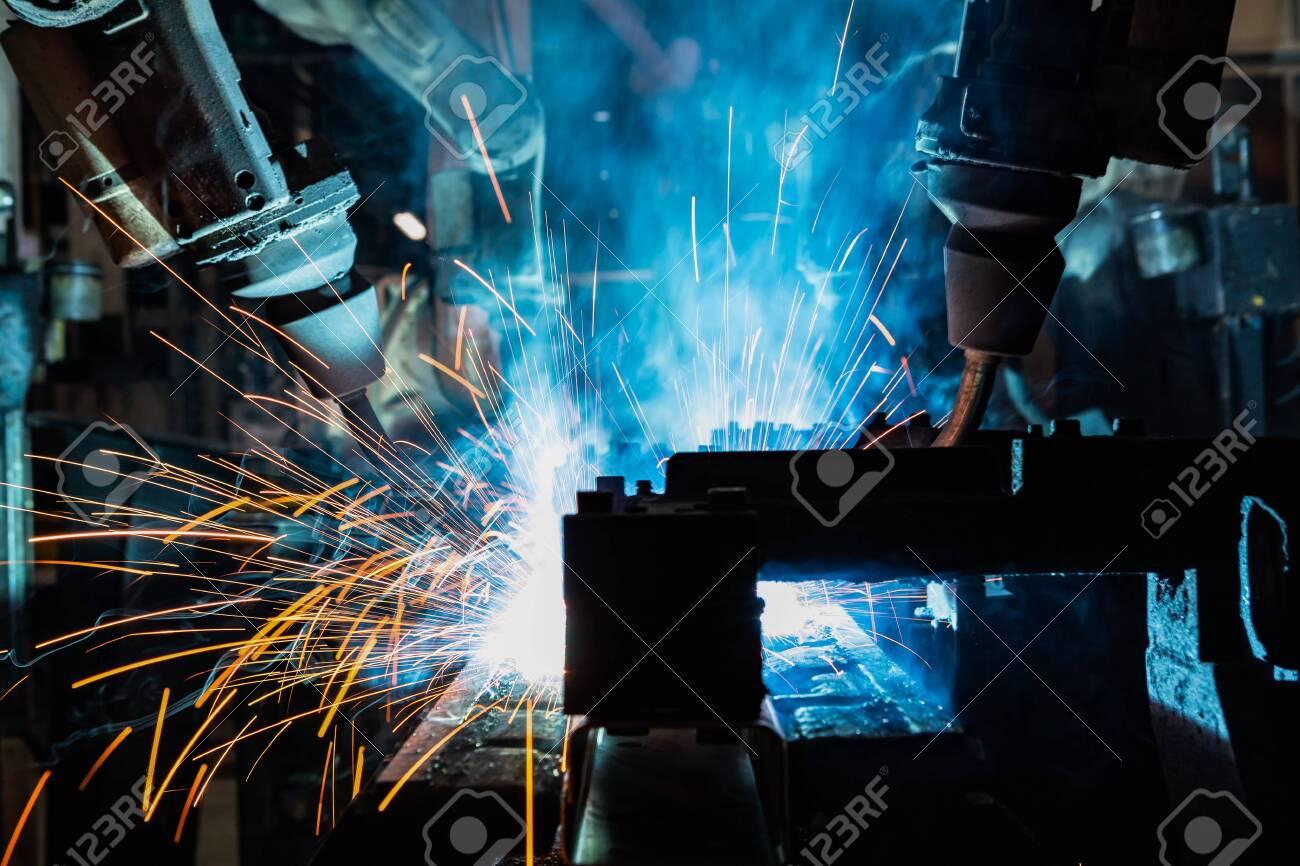 Team industrial robots are welding in factory - 153959544