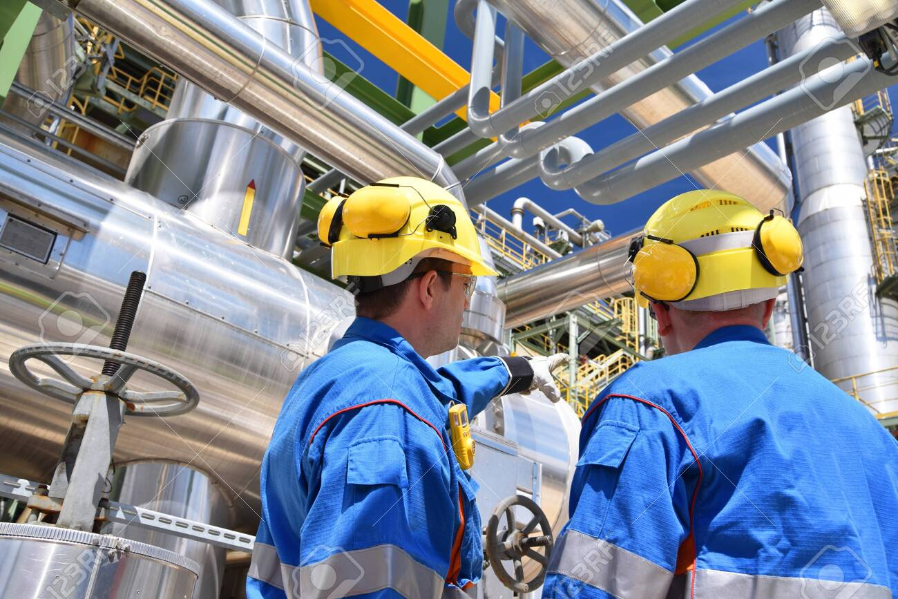 group of industrial workers in a refinery - oil processing equipment and machinery - 149656653