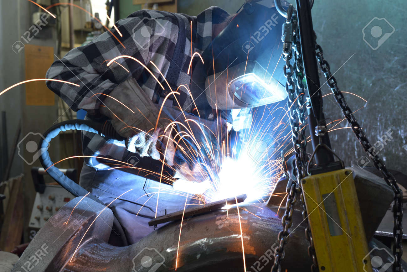Welder in protective clothing at the workplace in an industrial company in steel construction - 157026066