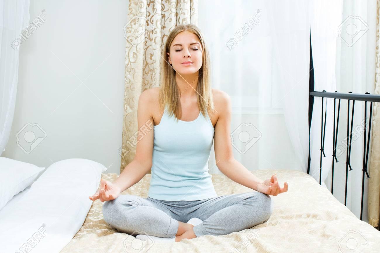 Il sesso migliora con gli ultrasuoni 27659018-Bella-donna-bionda-sta-meditando-sul-letto-nella-sua-camera-da-letto-Archivio-Fotografico