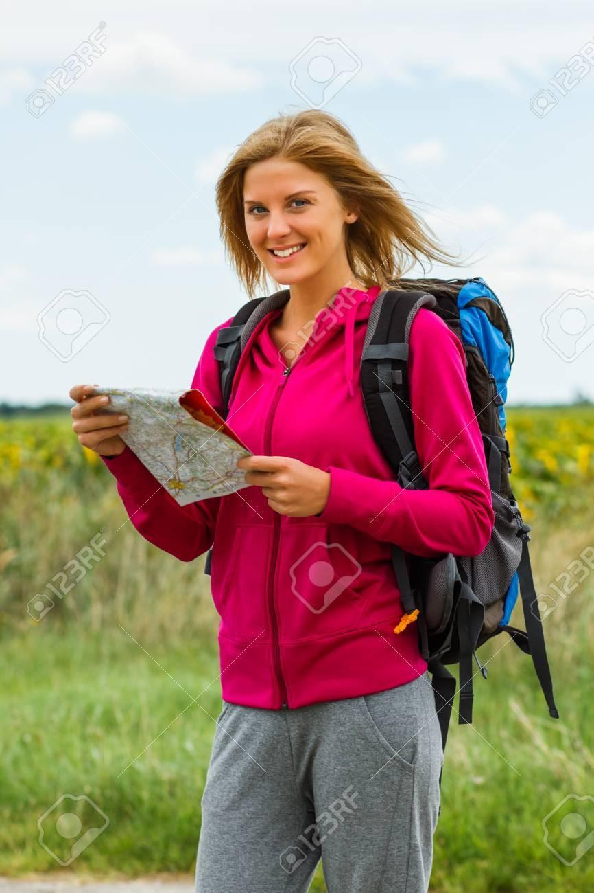 Mujer rubia alegre con mochila está sosteniendo un mapa que le ayudará a decidir qué camino tomar.