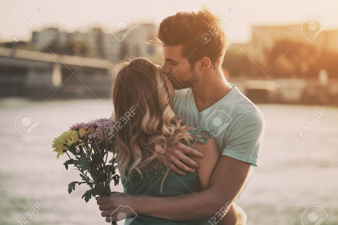 Young man is giving beautiful bouquet of flowers to his girlfriend.Image is intentionally toned. - 87957516