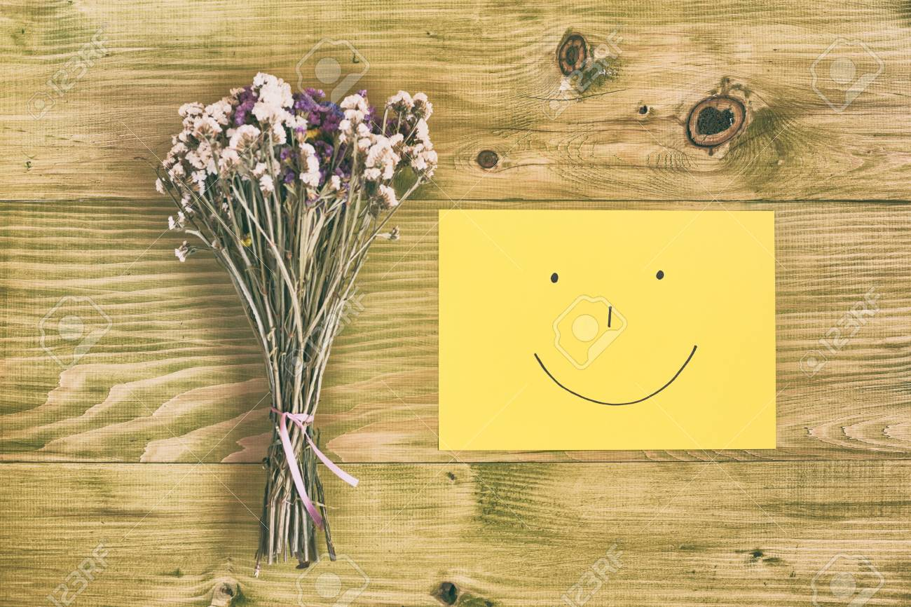 Beautiful bouquet of flowers and smiley face on wooden tableage beautiful bouquet of flowers and smiley face on wooden tableage is intentionally toned izmirmasajfo