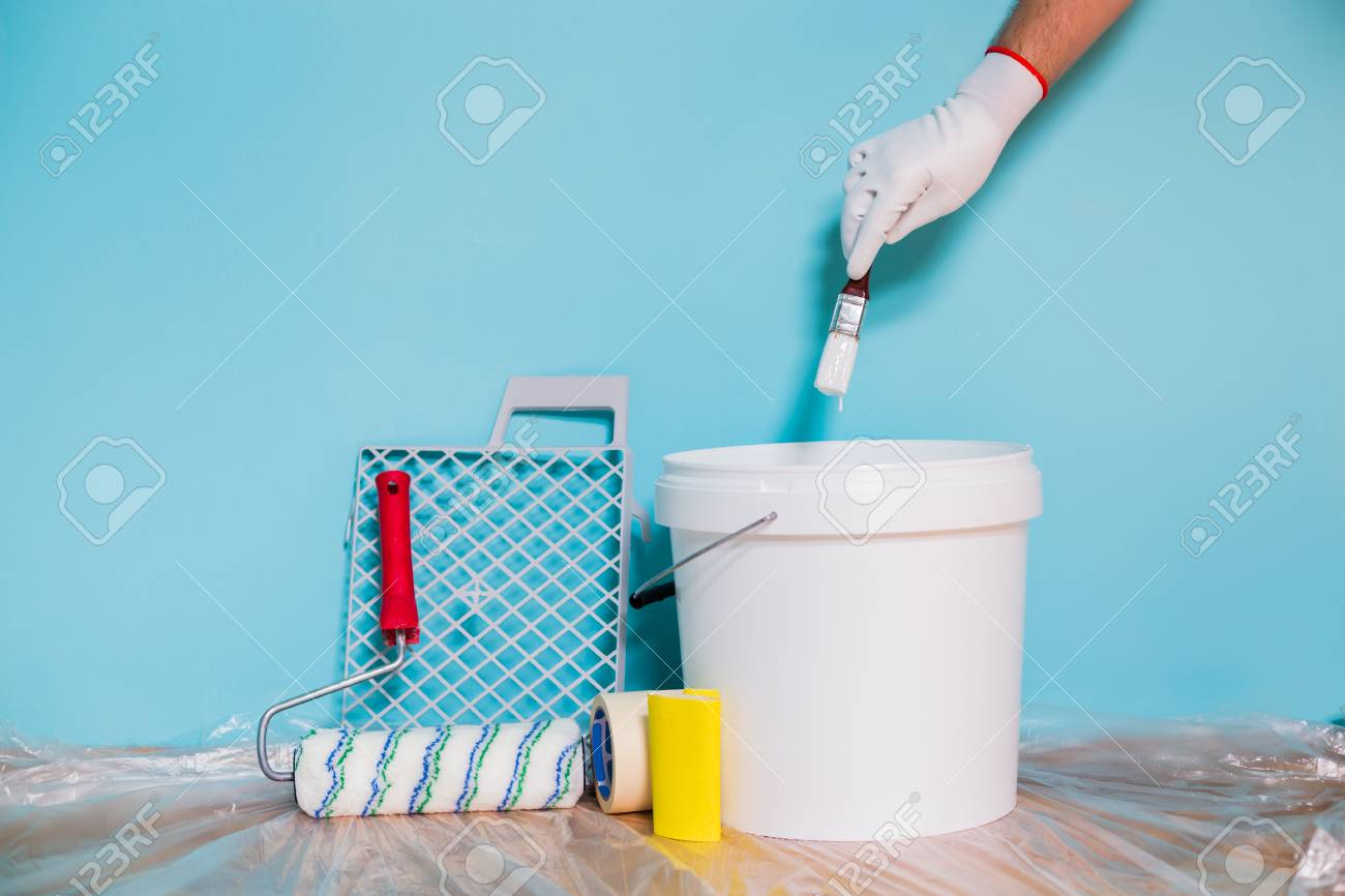 Image Of Equipment For Painting Wall And Man Holding Paintbrush