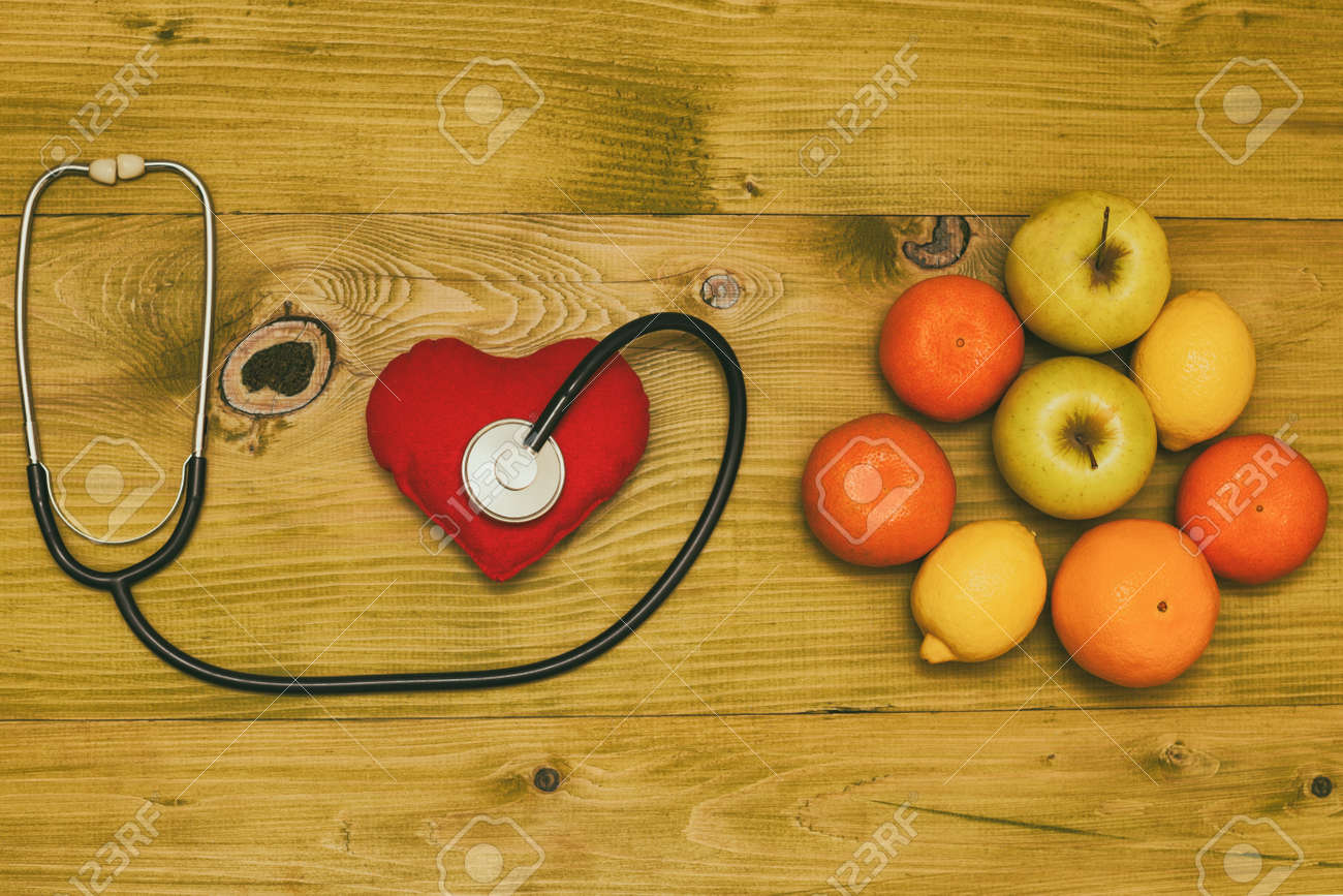 Image of fruit,stethoscope and heart shape on wooden table.Toned photo. - 121351674