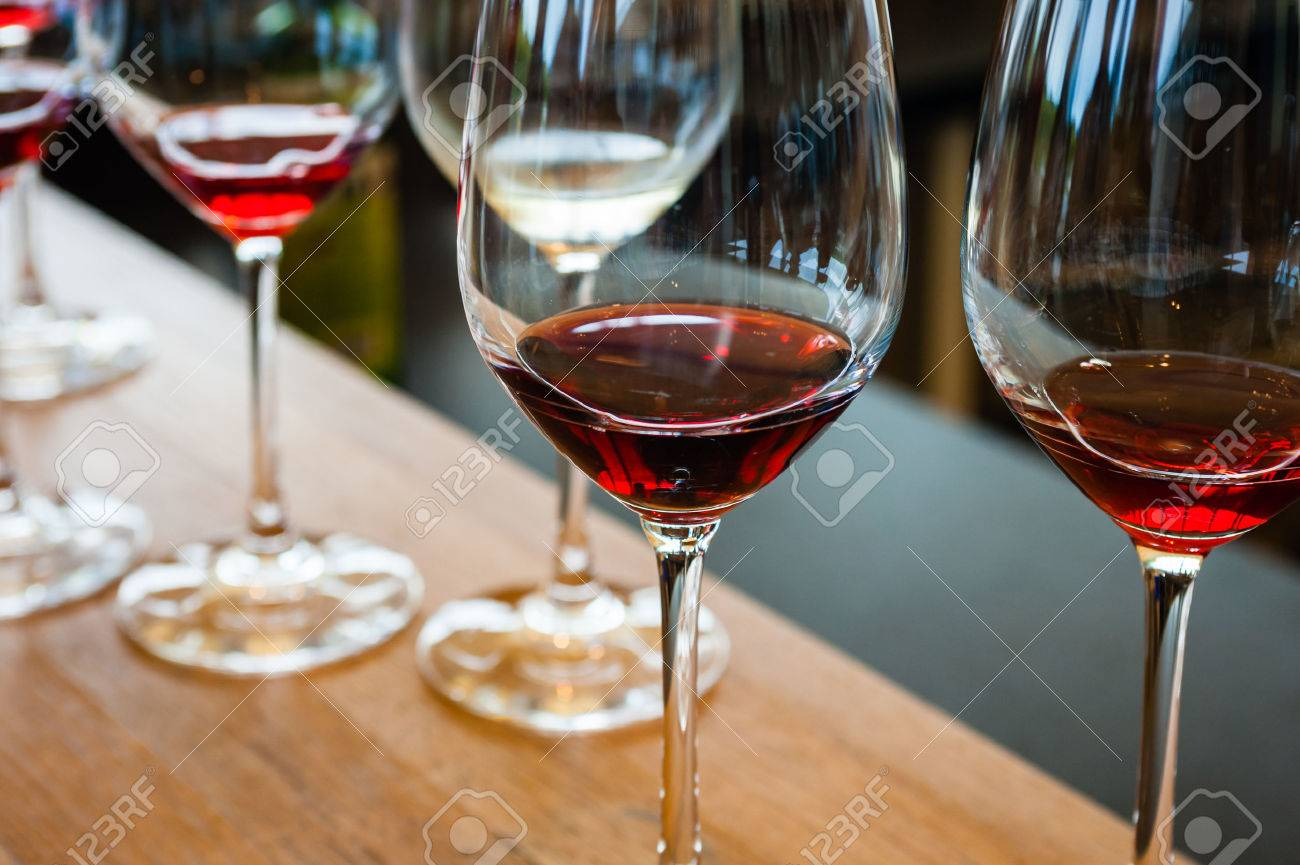 Detail of wine glasses with red wine samples, on wood counter with other glasses in background. - 52146861