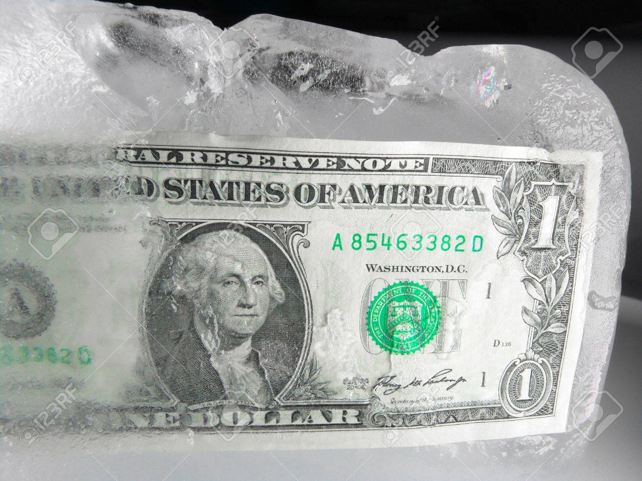 US paper currency (one dollar) in half frozen ice representing