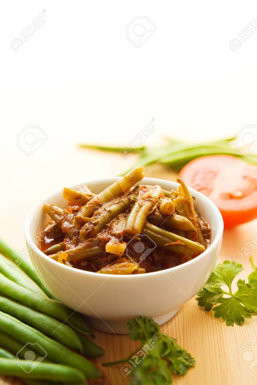 Green beans cooked in a spicy tomato sauce in a white bowl. Stock Photo - 12416600