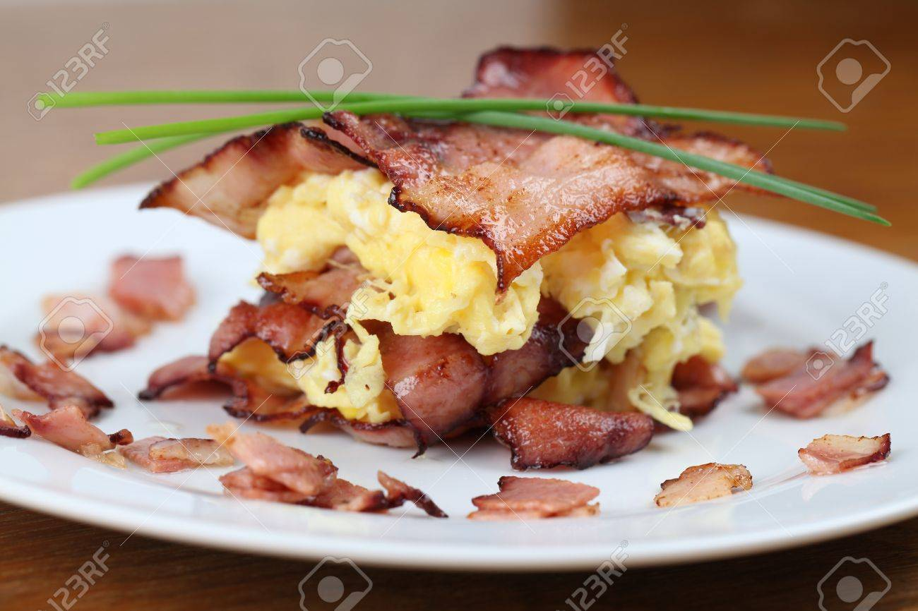 Scrambled eggs and bacon, garnished with chives on white plate Stock Photo - 8664485