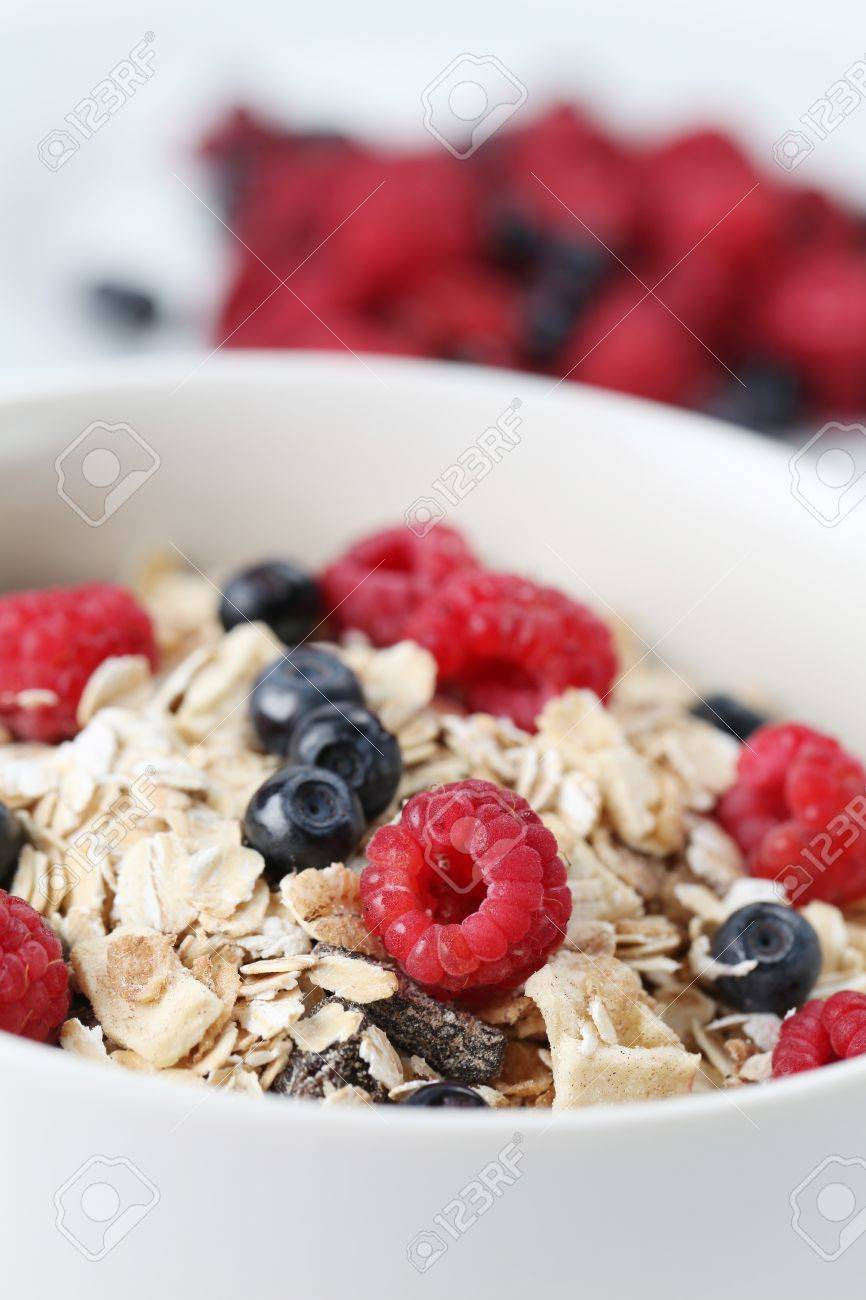 Granola with fresh organic raspberries and blueberries. Shallow DOF Stock Photo - 8772155