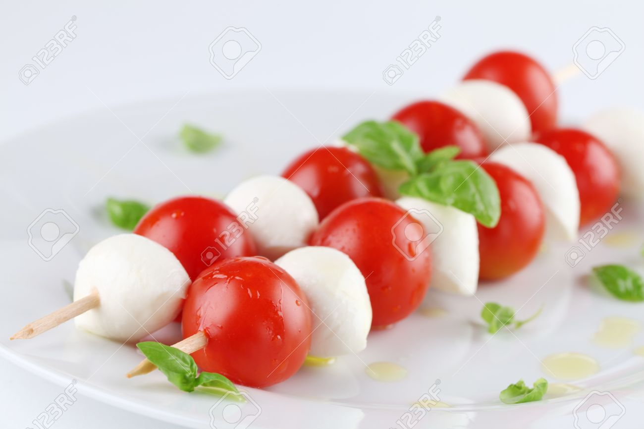 Caprese salad. Cherry tomatoes and mozzarella on skewers, garnished with basil leaves and olive oil Stock Photo - 8989386