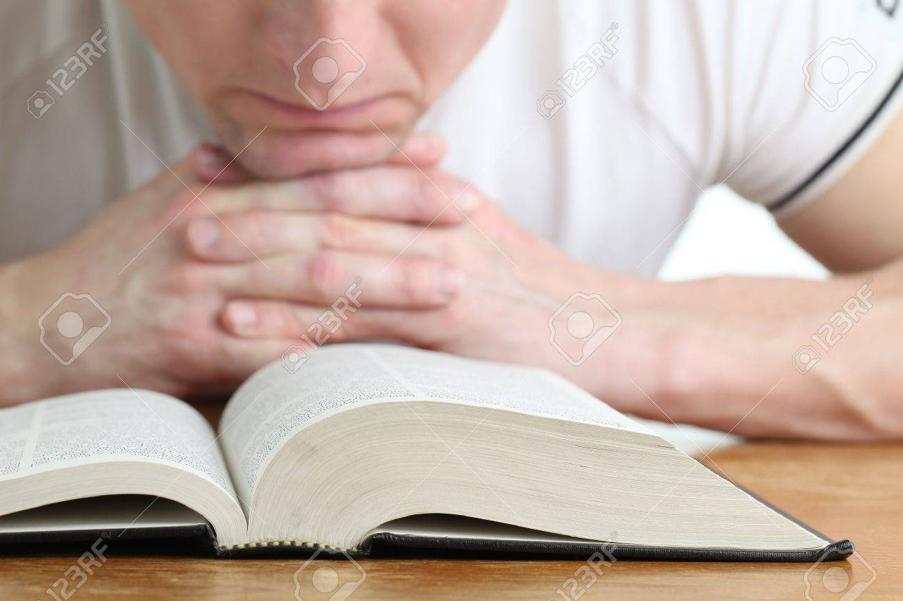 Man praying with the Bible. Focus on the Bible Stock Photo - 12542729