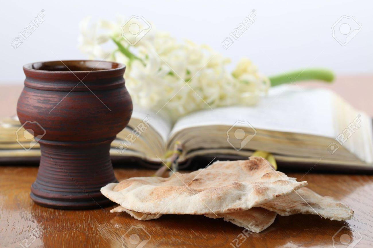 Communion. Chalice with red wine, pita bread, Holy Bible and white hyacinth Stock Photo - 12588106