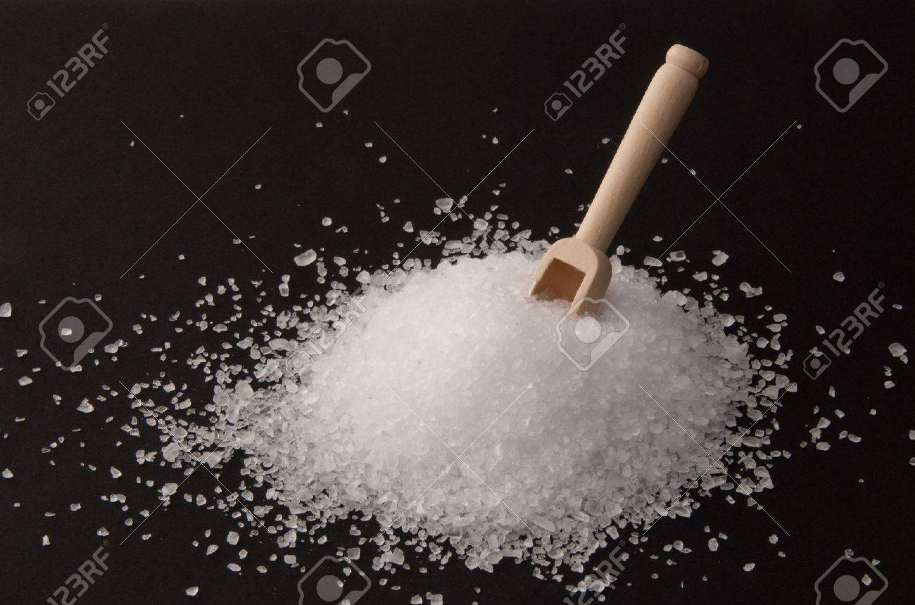 Coarse-grained sea salt from the Atlantic with a wooden sccop on black background Standard-Bild - 9826886
