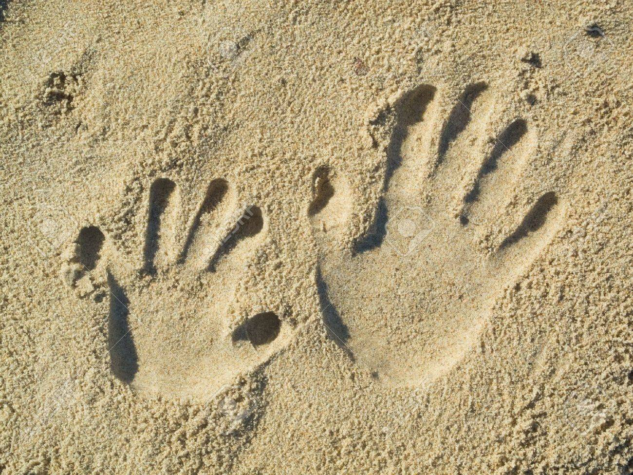 Optical illusion - Handprints of a child and an adult in the sand Standard-Bild - 13284992