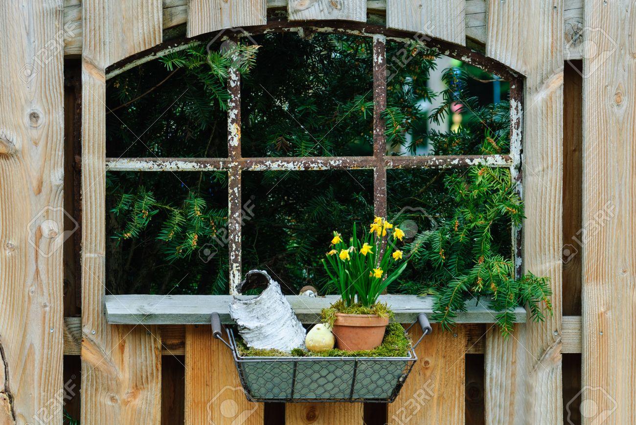 Vieille fenêtre de grange dans une clôture de jardin en bois avec  décoration en osier