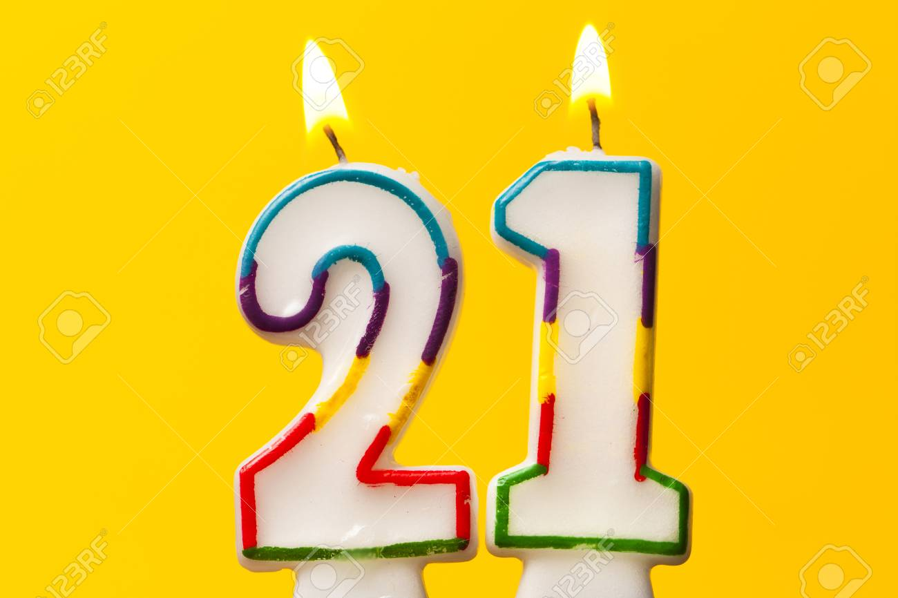 Number 21 Birthday Celebration Candle Against A Bright Yellow Background Stock Photo