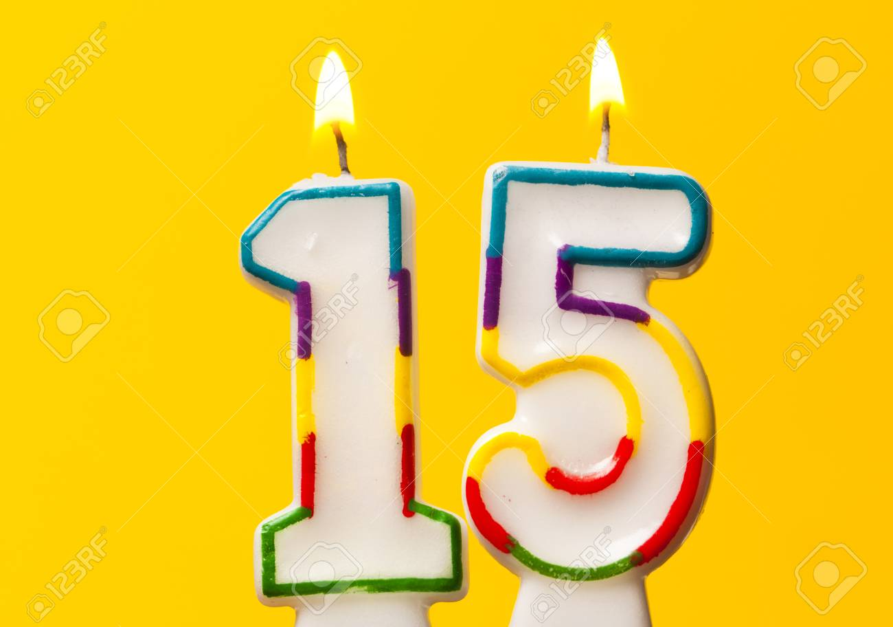 Number 15 Birthday Celebration Candle Against A Bright Yellow Background Stock Photo