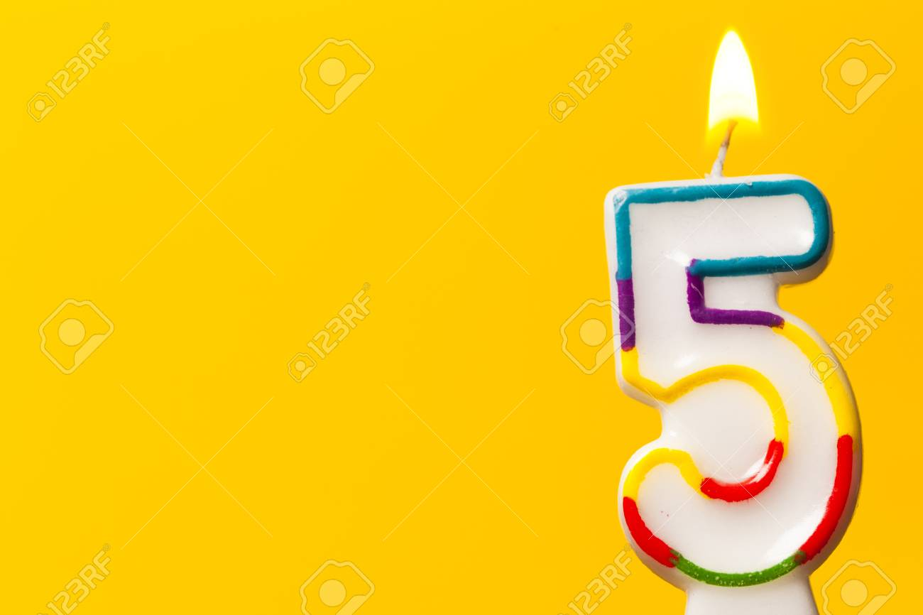 Number 5 Birthday Celebration Candle Against A Bright Yellow Background Stock Photo