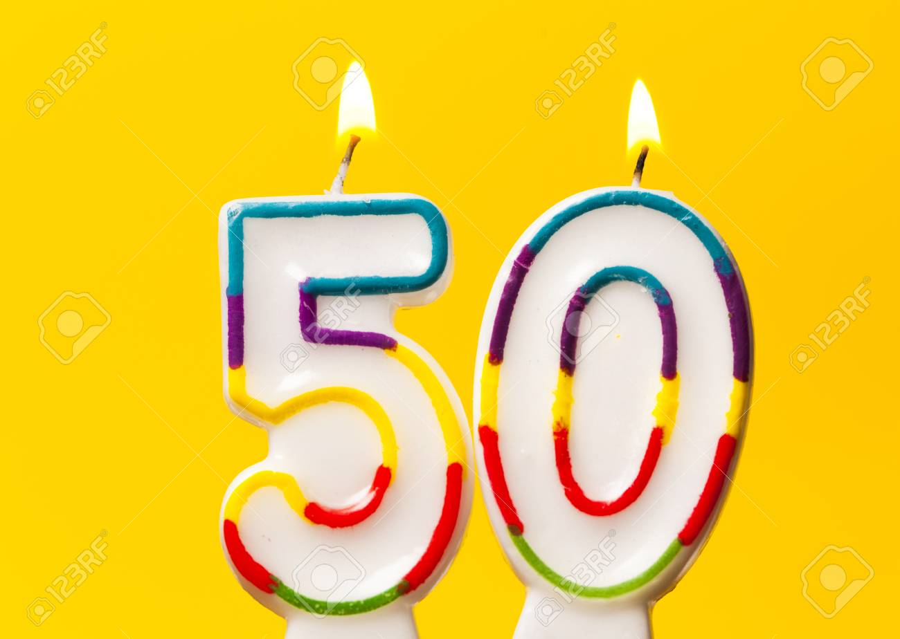 Number 50 birthday celebration candle against a bright yellow background - 91707853