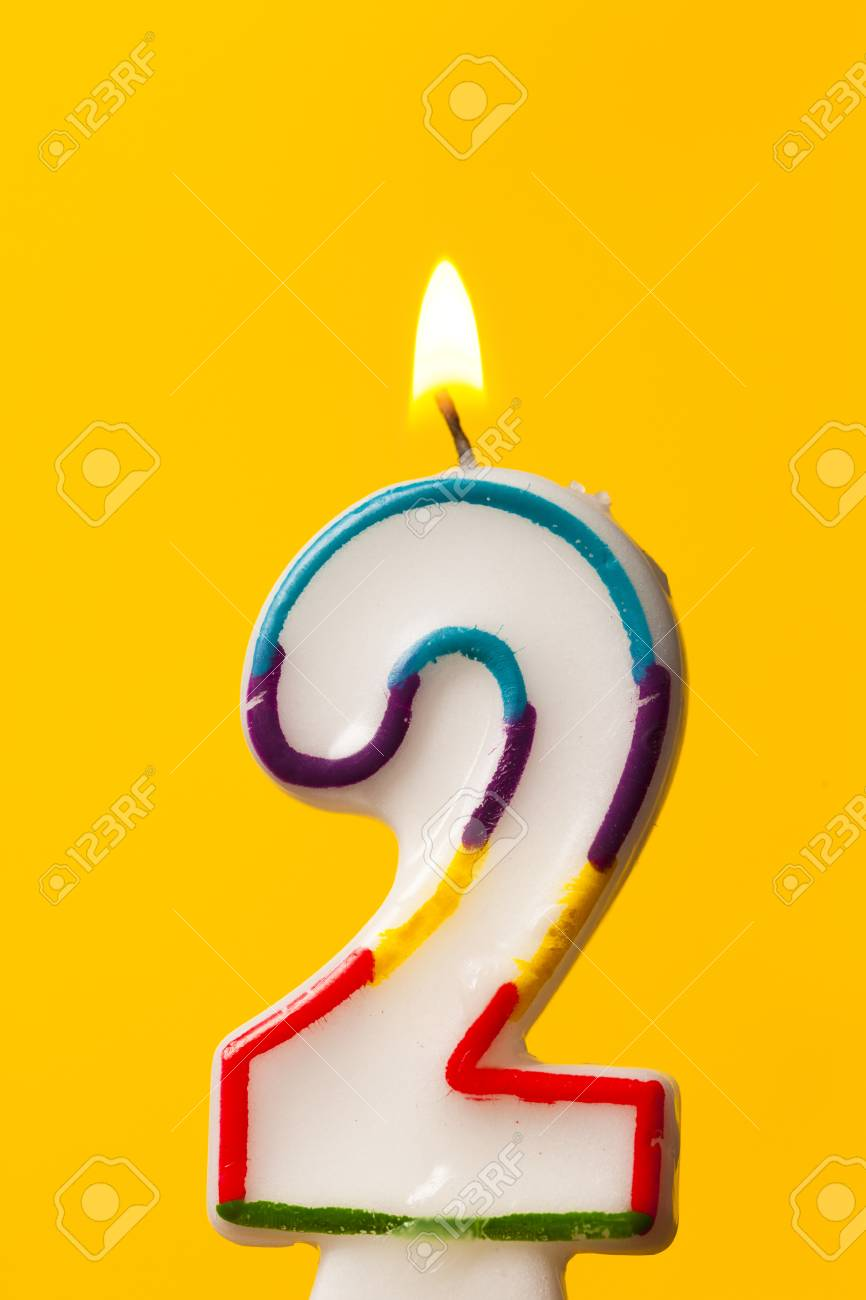 Number 2 Birthday Celebration Candle Against A Bright Yellow Background Stock Photo