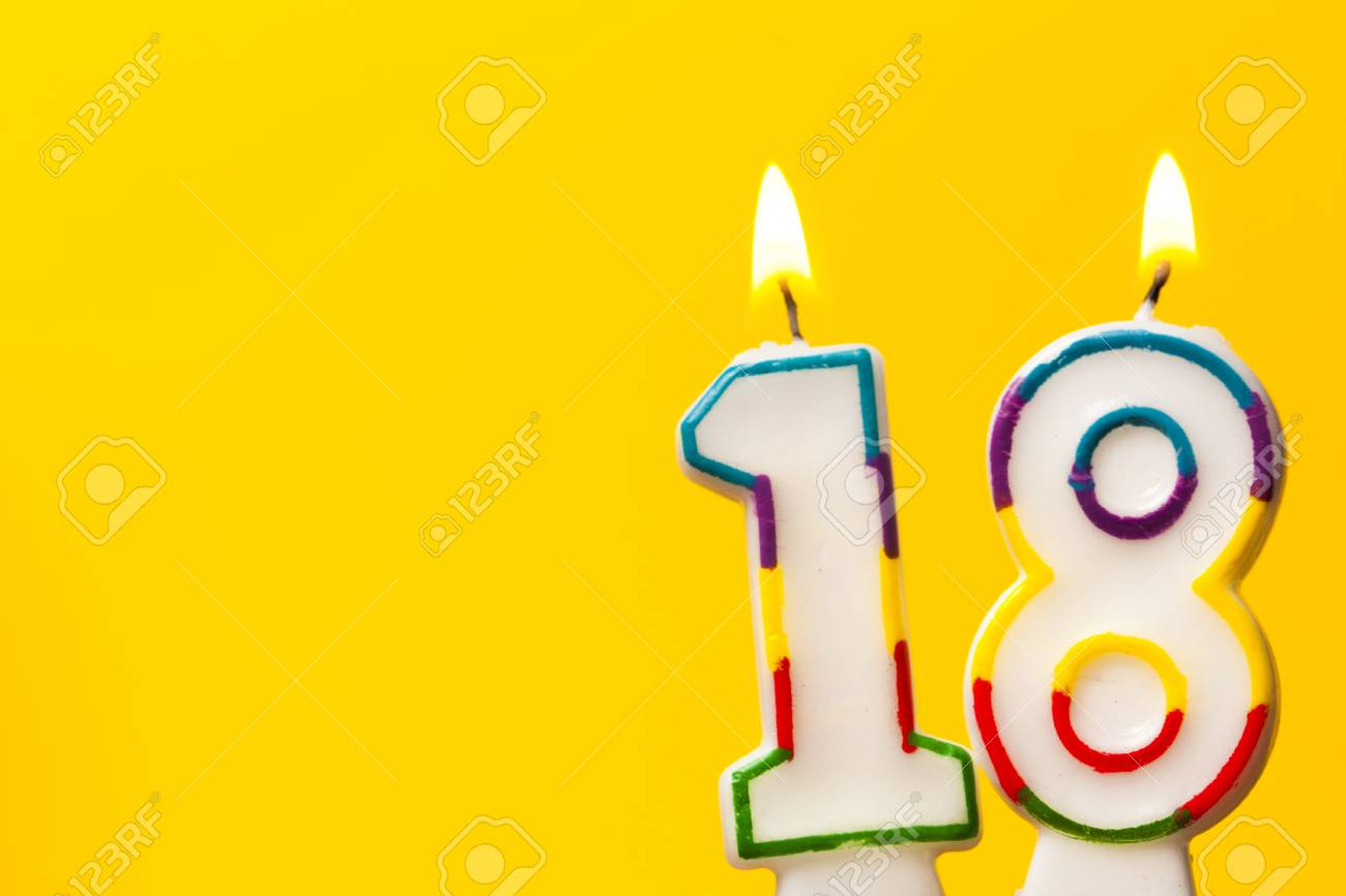 Number 18 Birthday Celebration Candle Against A Bright Yellow Background Stock Photo