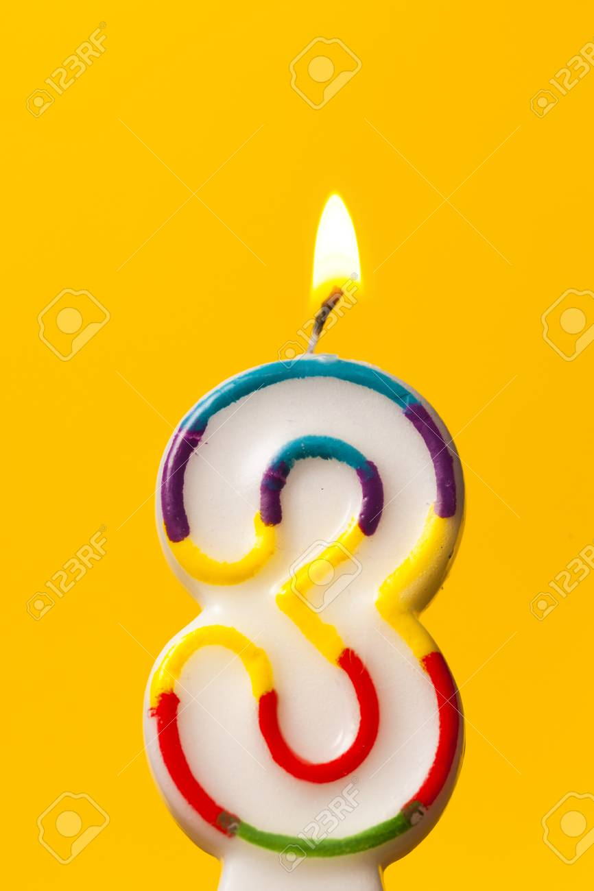 Number 3 Birthday Celebration Candle Against A Bright Yellow Background Stock Photo