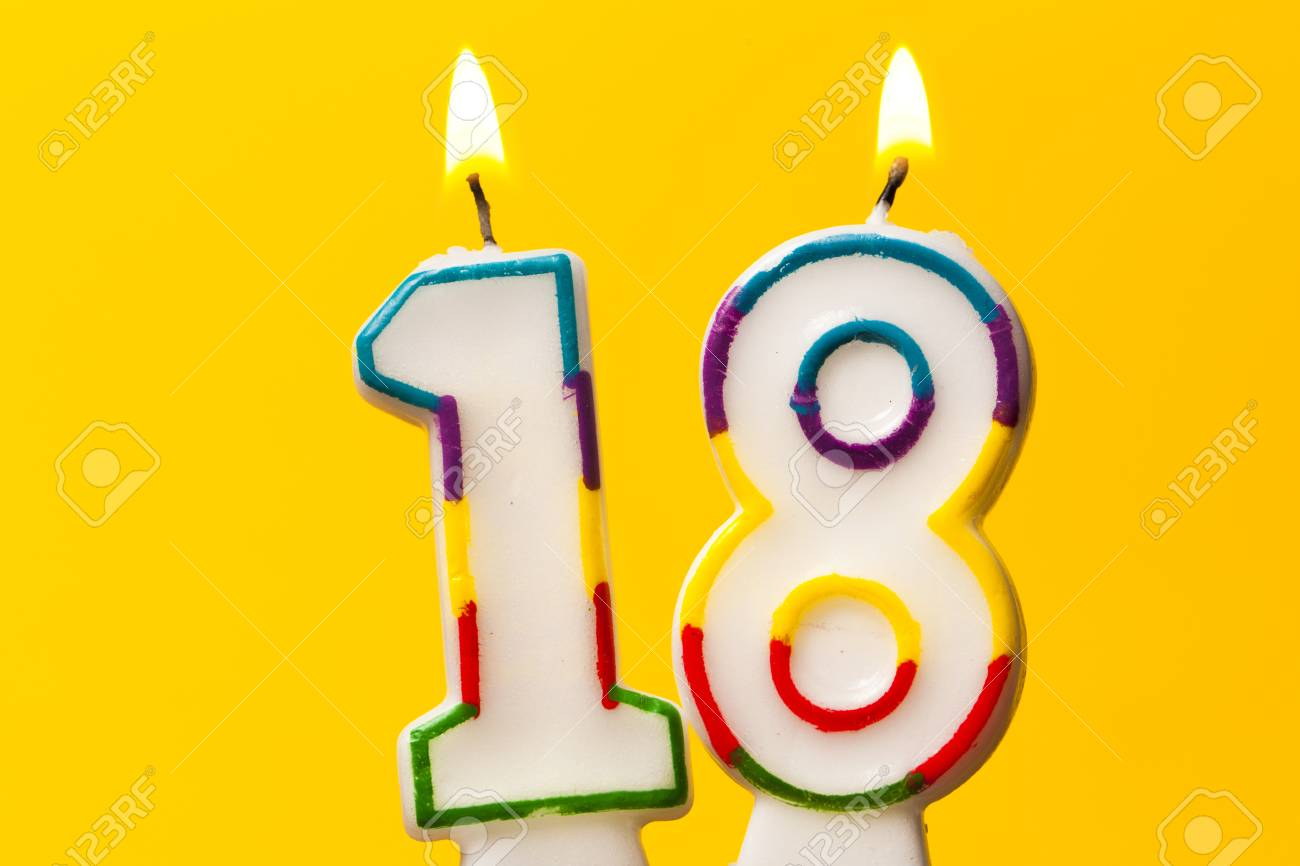 Number 18 birthday celebration candle against a bright yellow background - 91707506