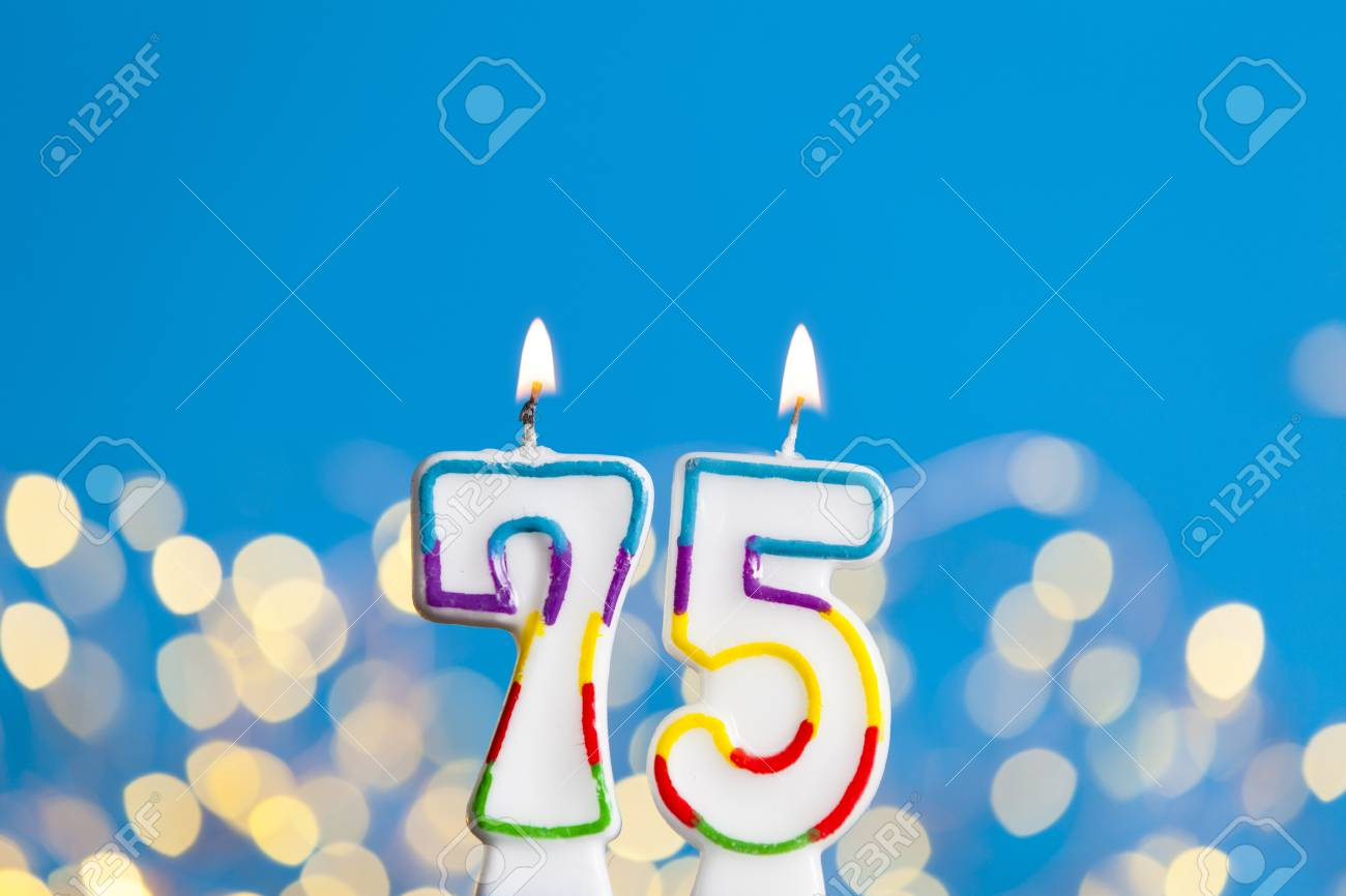 Number 75 Birthday Celebration Candle Against A Bright Lights And Blue Background Stock Photo