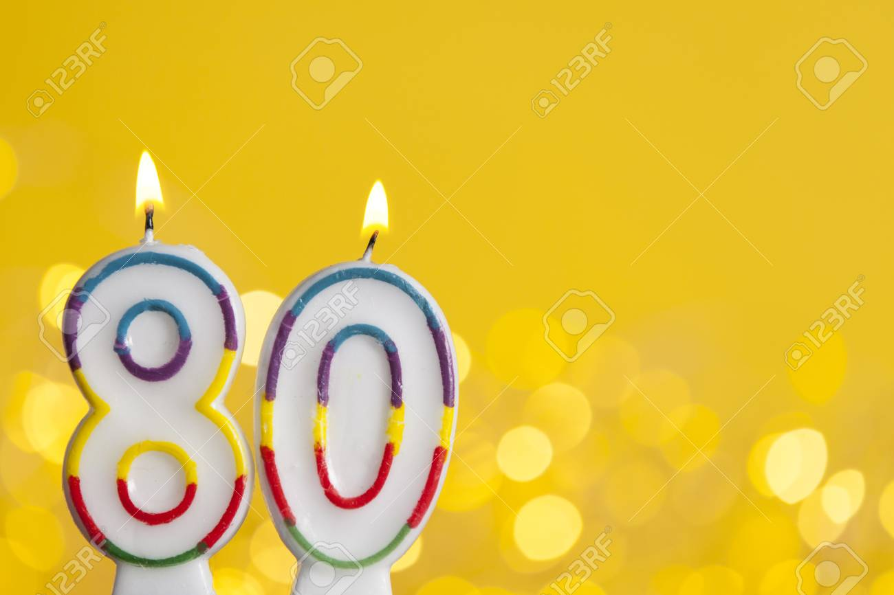 Number 80 Birthday Celebration Candle Against A Bright Lights And Yellow Background Stock Photo