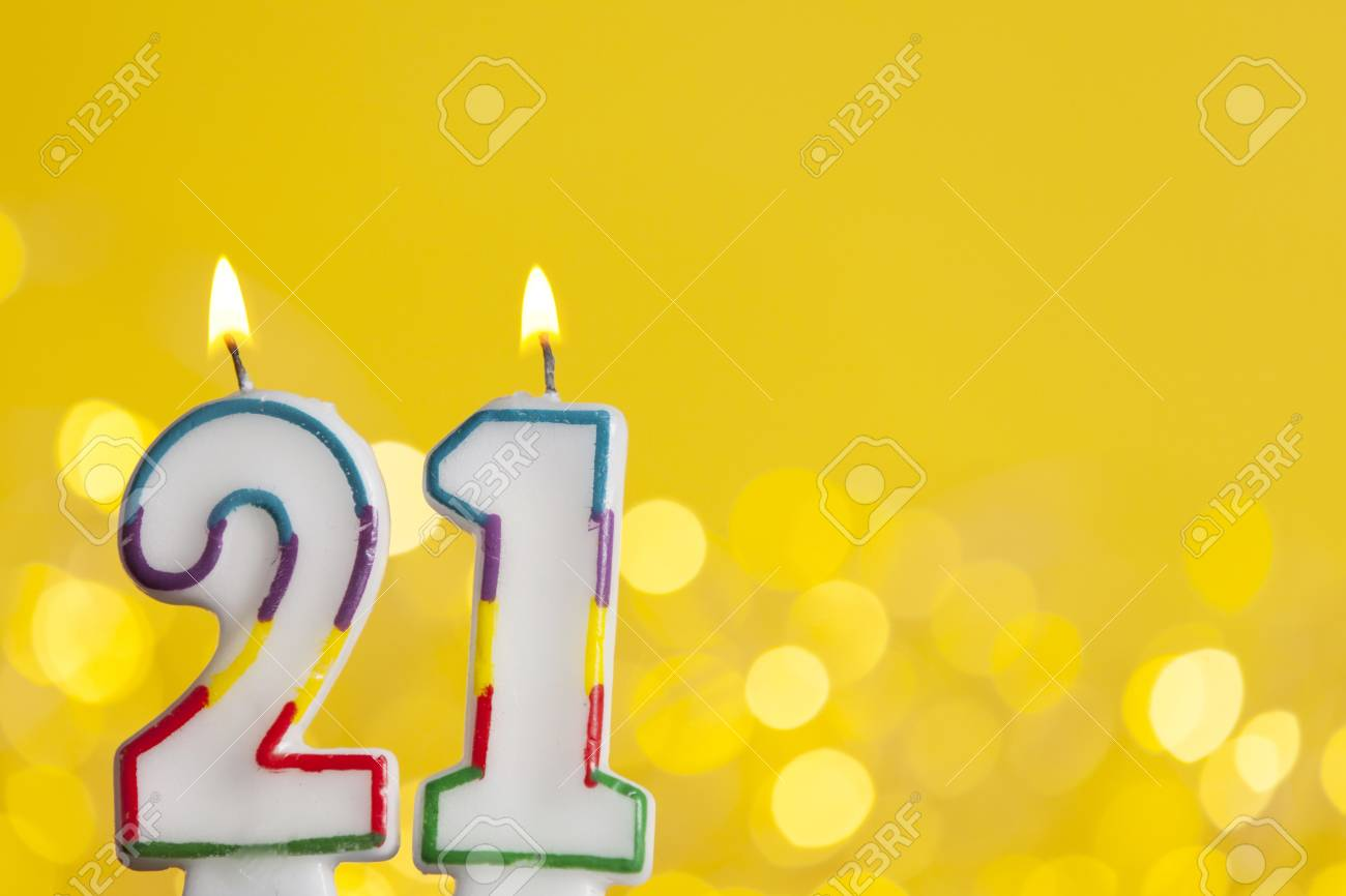 Number 21 Birthday Celebration Candle Against A Bright Lights And Yellow Background Stock Photo