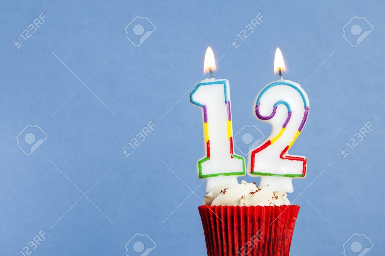 Number 12 Birthday Candle In A Cupcake Against Blue Background Stock Photo