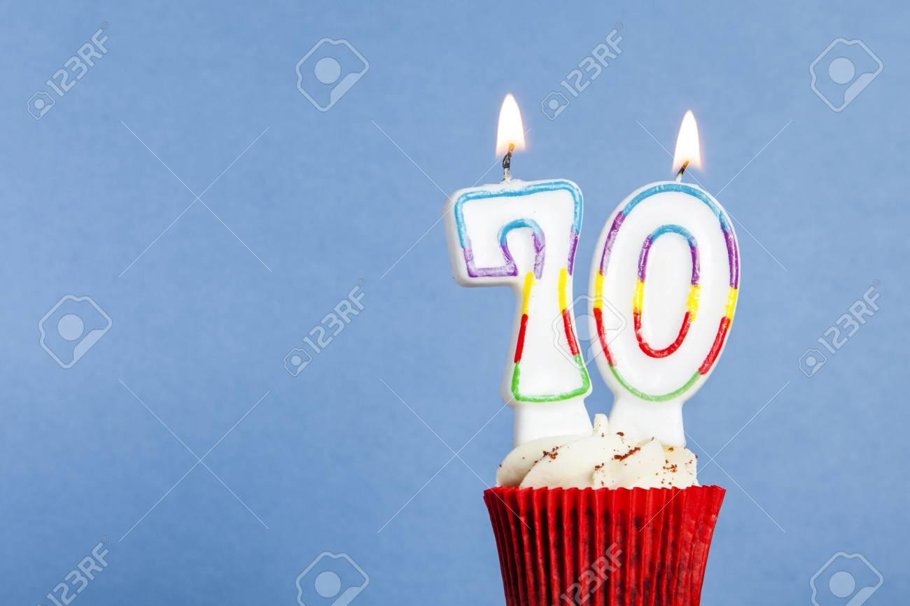 Number 70 Birthday Candle In A Cupcake Against Blue Background Stock Photo