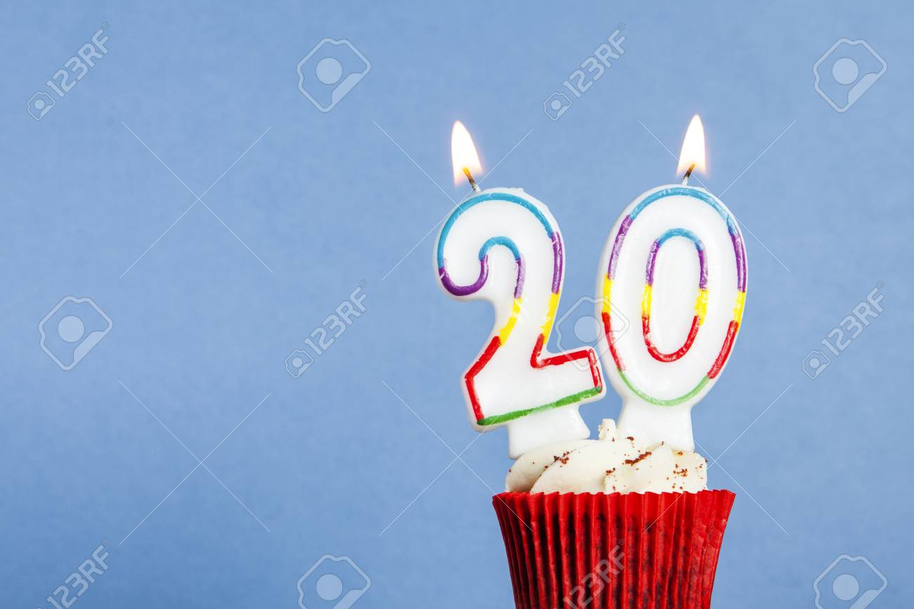 Number 20 birthday candle in a cupcake against a blue background - 95834862
