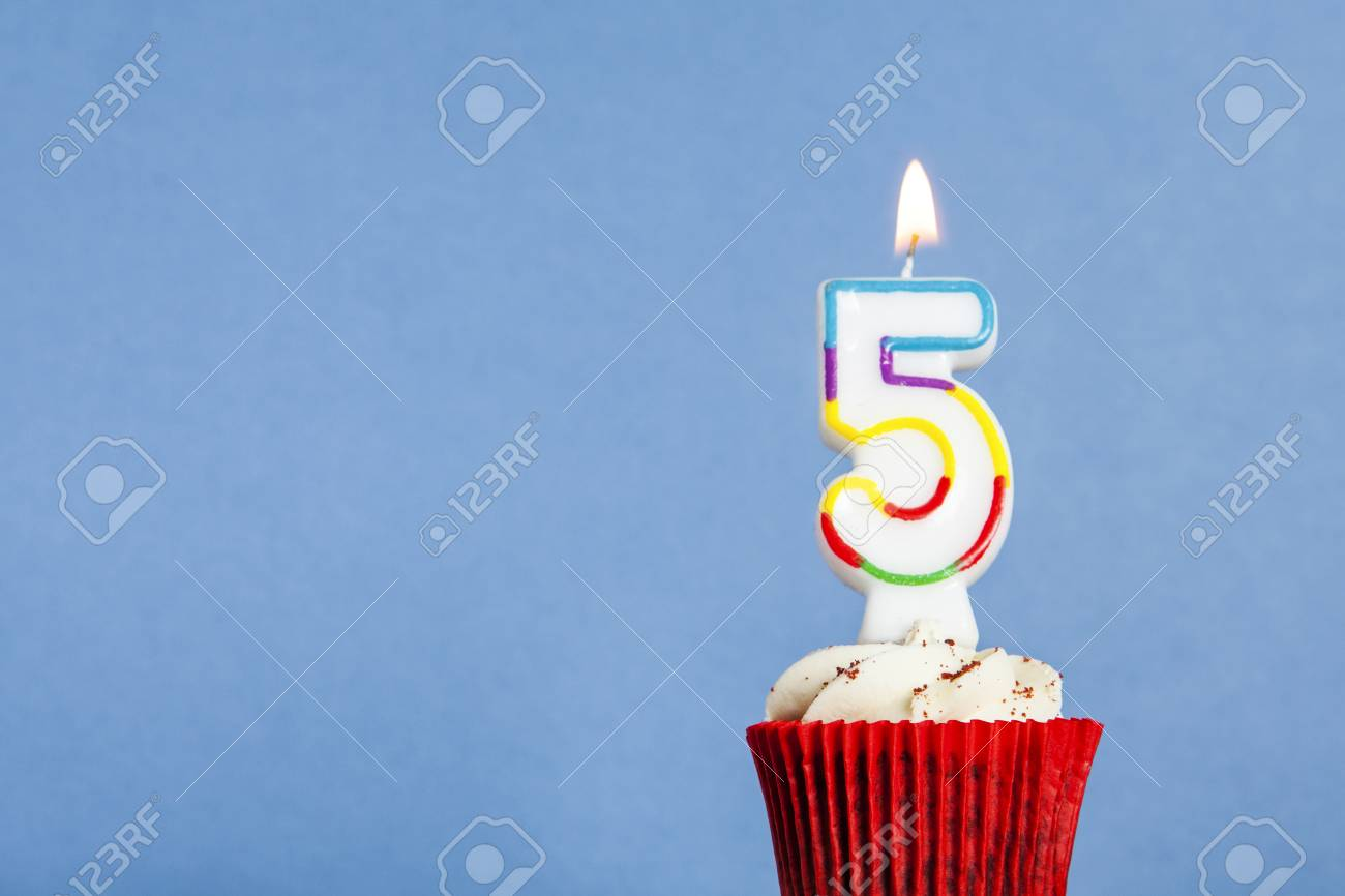 Number 5 Birthday Candle In A Cupcake Against Blue Background Stock Photo