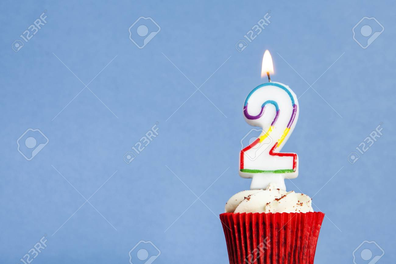 Number 2 Birthday Candle In A Cupcake Against Blue Background Stock Photo