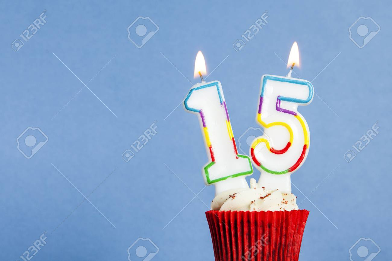 Number 15 Birthday Candle In A Cupcake Against Blue Background Stock Photo