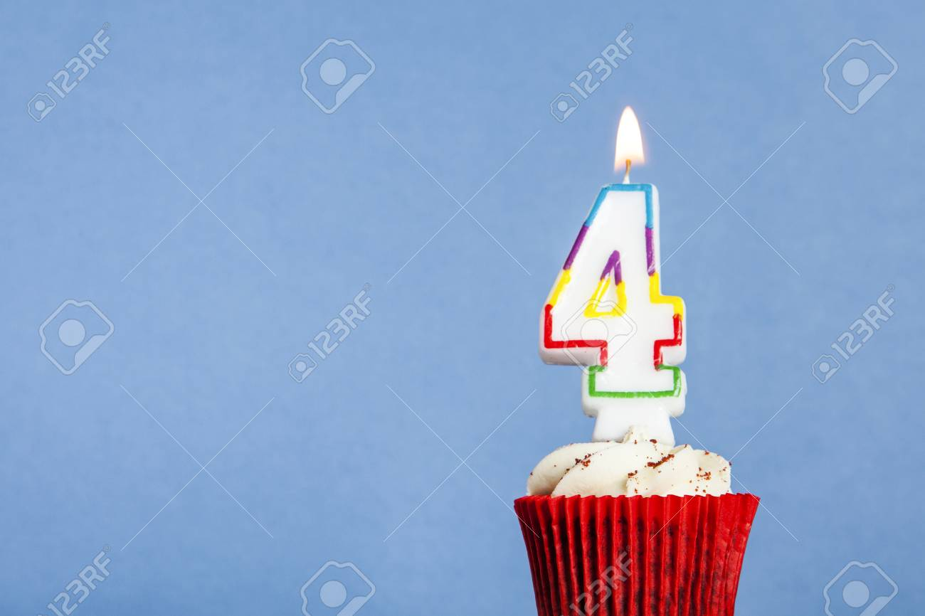 Number 4 Birthday Candle In A Cupcake Against Blue Background Stock Photo