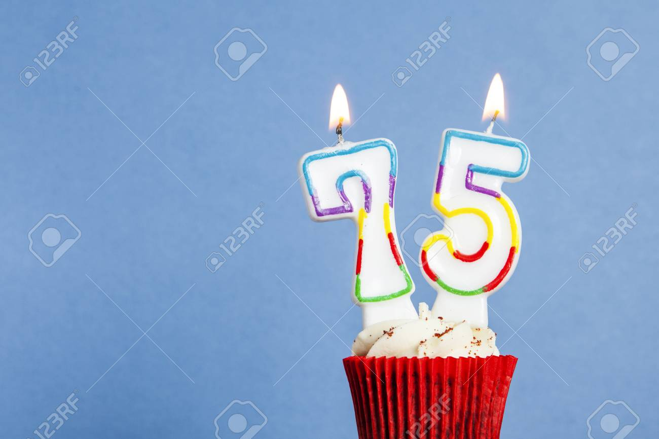 Number 75 Birthday Candle In A Cupcake Against Blue Background Stock Photo
