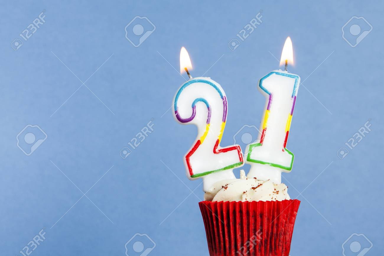 Number 21 Birthday Candle In A Cupcake Against Blue Background Stock Photo
