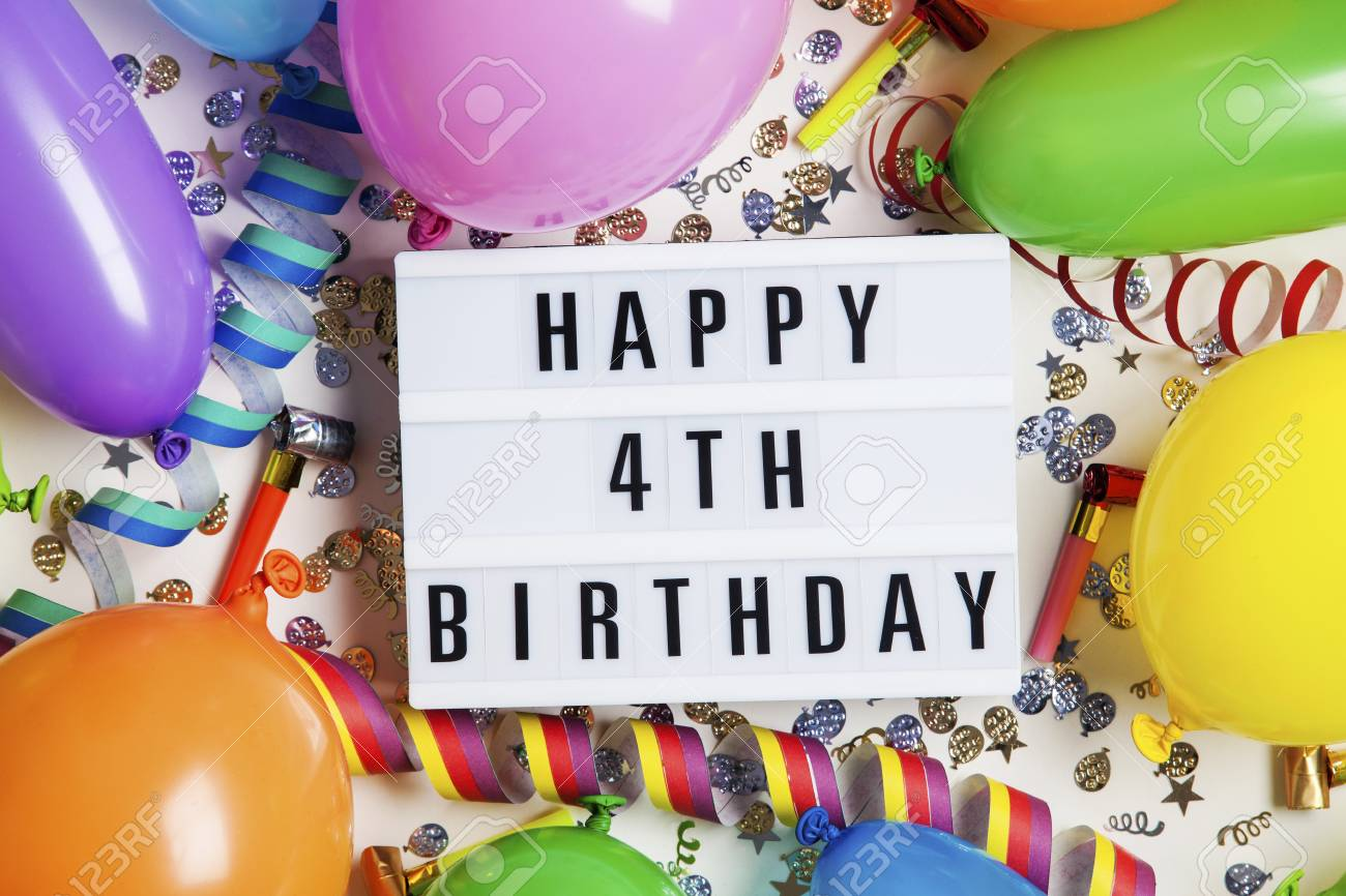 Happy 4th Birthday Celebration Message On A Lightbox With Balloons And Confetti Stock Photo