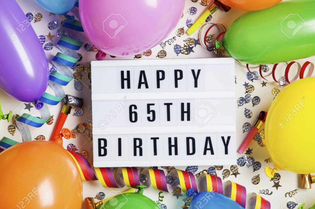 Happy 65th Birthday Celebration Message On A Lightbox With Balloons And Confetti Stock Photo
