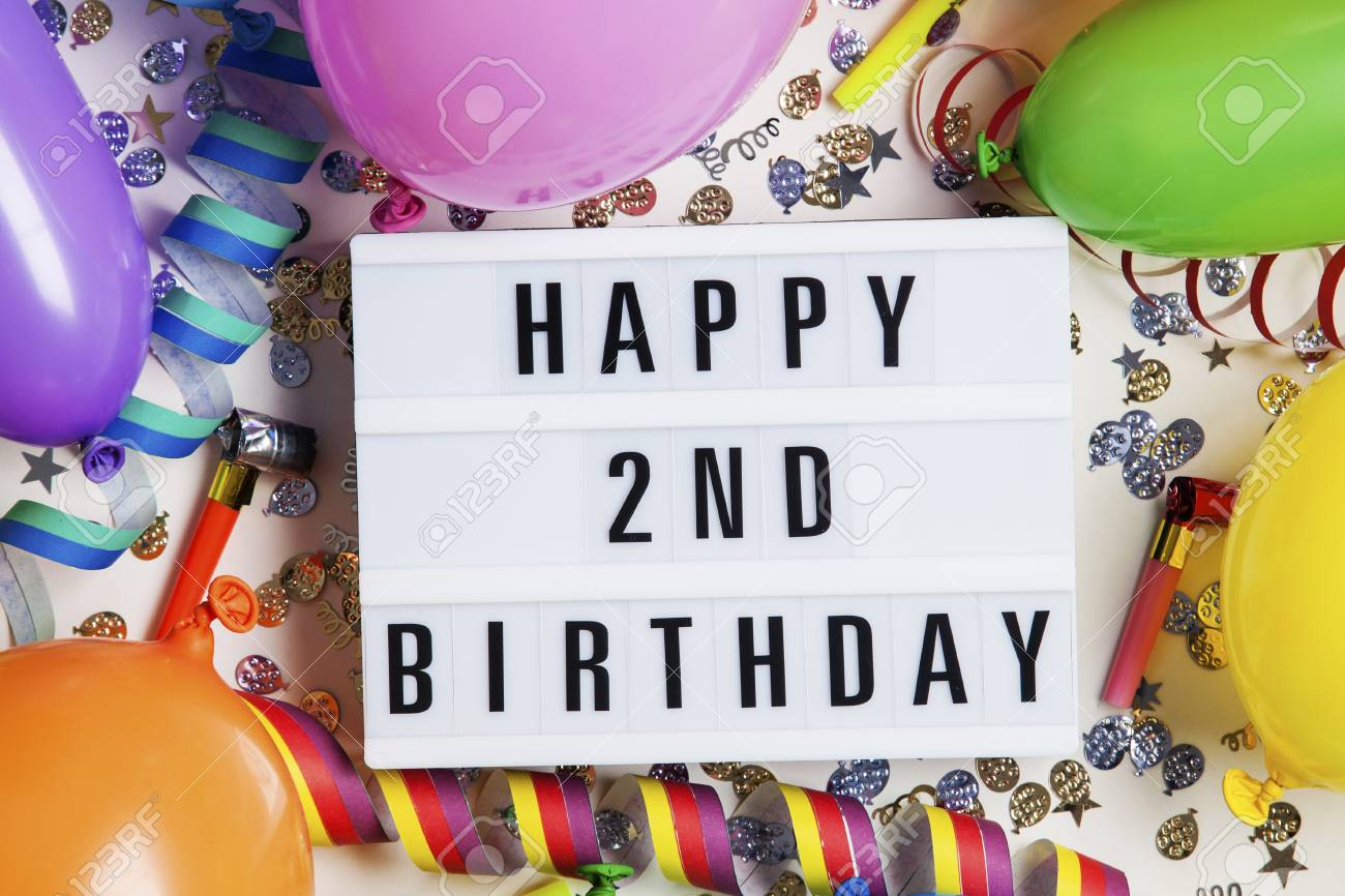 Happy 2nd Birthday Celebration Message On A Lightbox With Balloons And Confetti Stock Photo