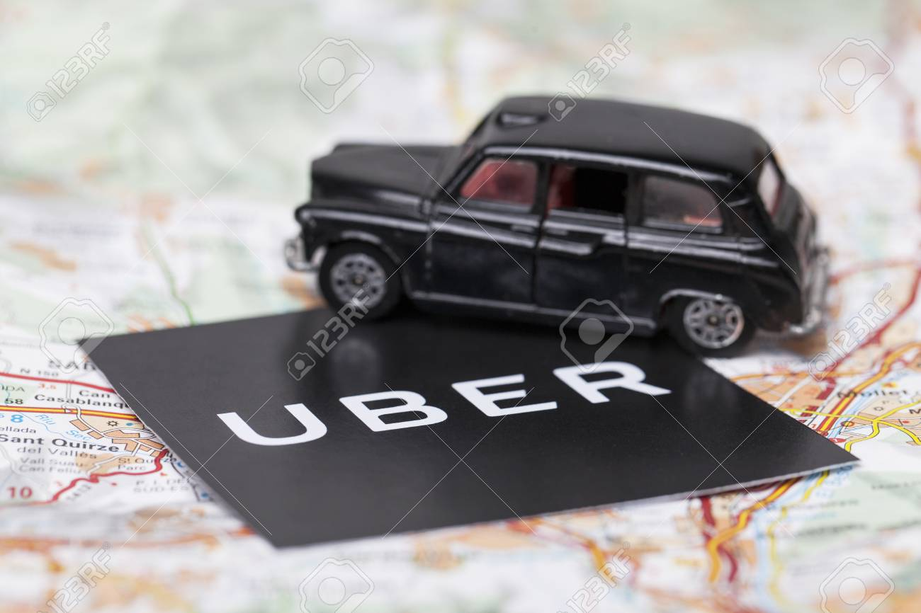 London, UK - MARCH 23rd 2017: A photograph of the Uber logo with a black London style taxi toy car. Uber is a popular taxi style transport service application, founded in 2009 - 104328395