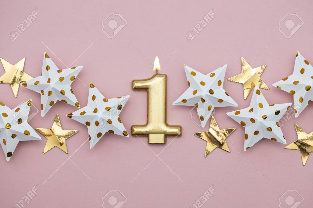 Number 1 gold candle and stars on a pastel pink background - 112643180