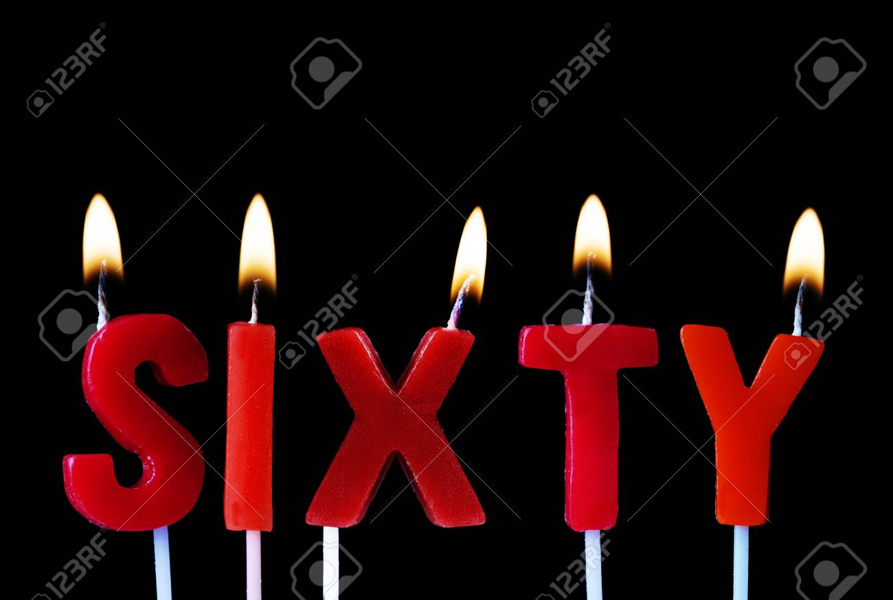 Sixty Spell Out In Red Birthday Candles Against A Black Background