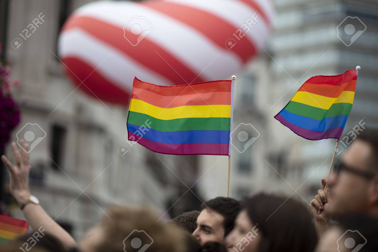 LONDON, UK - July 6th 2019: People wave LGBTQ pride flags at a solidarity march - 130821344